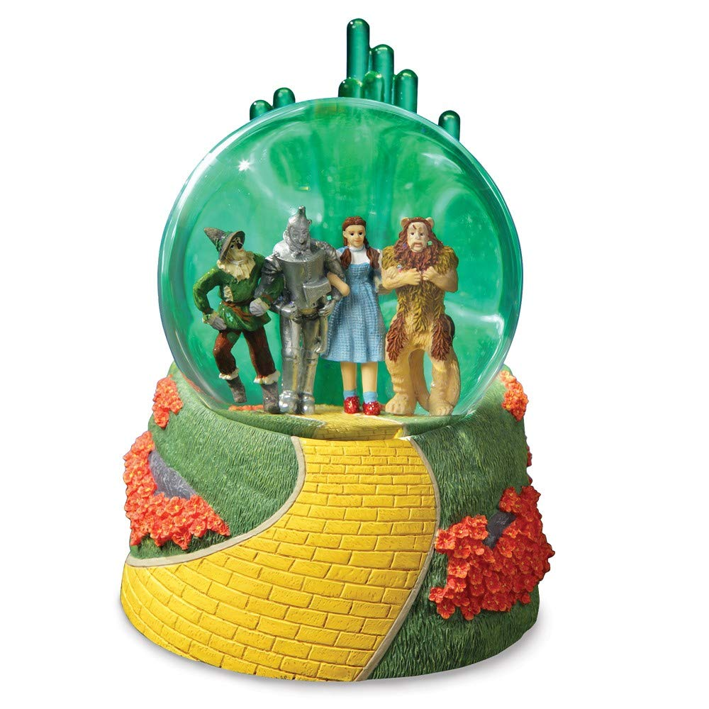 Four friends in water globe on the yellow brick road with glowing Emerald City in the background.