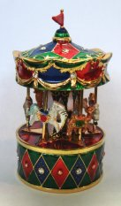 Miniature revolving musical carousel on red and green base