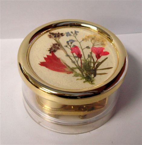 Clear round lucite music box with dried Swiss flowers.
