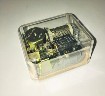 Robbins mechanism in clear plastic casing with wood base